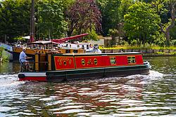 A narrowboat makes its way along the River Thames at Old Windsor, Berkshire. Old Windsor, Berkshire, July 05 2019.