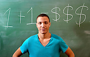 A young man on a college campus with a chalkboard and a comment about the cost of education.