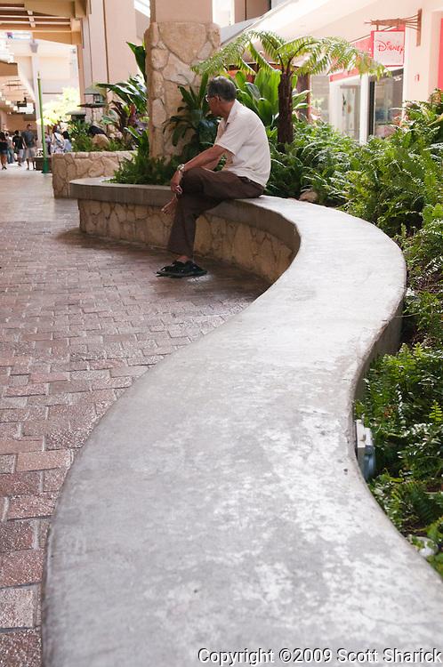 A man sits waiting at a local mall.