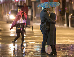 Licensed to London News Pictures. 10/10/2020. London, UK. A couple kiss in the rain on Saturday night at Leicester Square, central London. After the 10pm curfew early closing of pubs and bars. Photo credit: Marcin Nowak/LNP