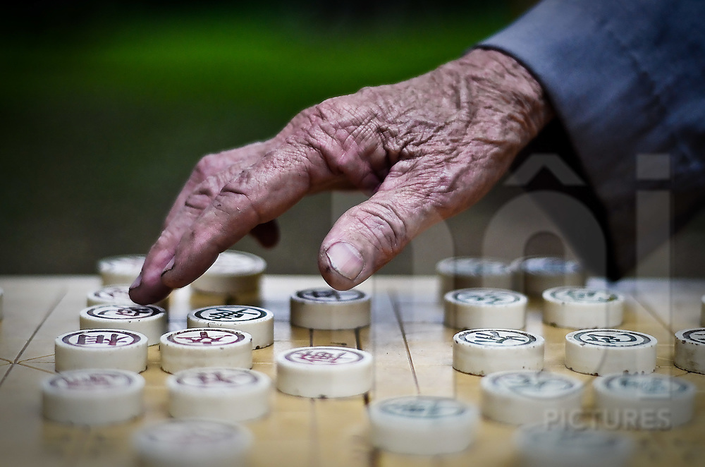 Wrinkled hand moves a pawn on a Chinese checker's board game in a Hanoi park, Vietnam, Southeast Asia