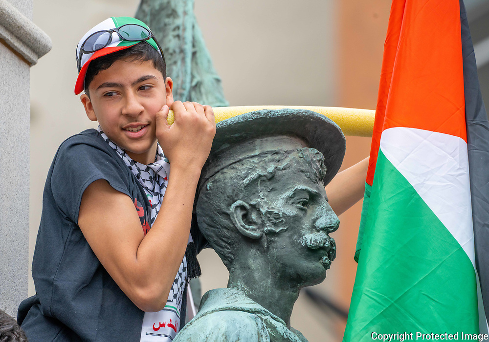 Flying the flag of Palestine, Mehdee Abdelaziz, 13, of Allentown, sits on top of the war memorial during a Palestine solidarity rally in downtown Allentown, Pennsylvania.