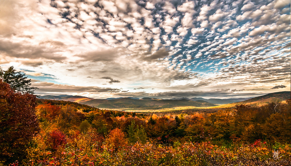 SUBJECT: White Mountains, New Hampshire from the Bear Notch Road IMAGE: With Mount Washington in clouds on the western horizon, sunlight dapples the White Mountains and valleys of New Hampshire in late afternoon of a Fall day. Snow fell on the mountaintops overnight.