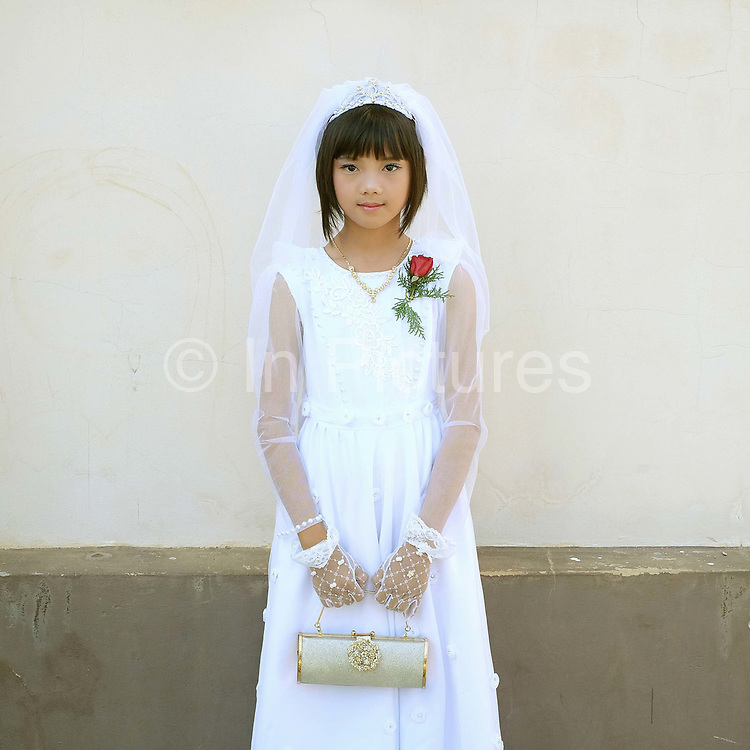 Portrait of Innocent, a ten year old ethnic Kayan girl at her first communion at Christ the King Cathedral in Loikaw, Kayah State, Myanmar on 20th November 2016. In the past most people residing in Kayah State were traditional spirit worshippers, but significant numbers have converted to Christianity, especially Baptist or Catholic