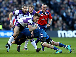 Scotland's Huw Jones (left) is tackled during the NatWest 6 Nations match at BT Murrayfield, Edinburgh.
