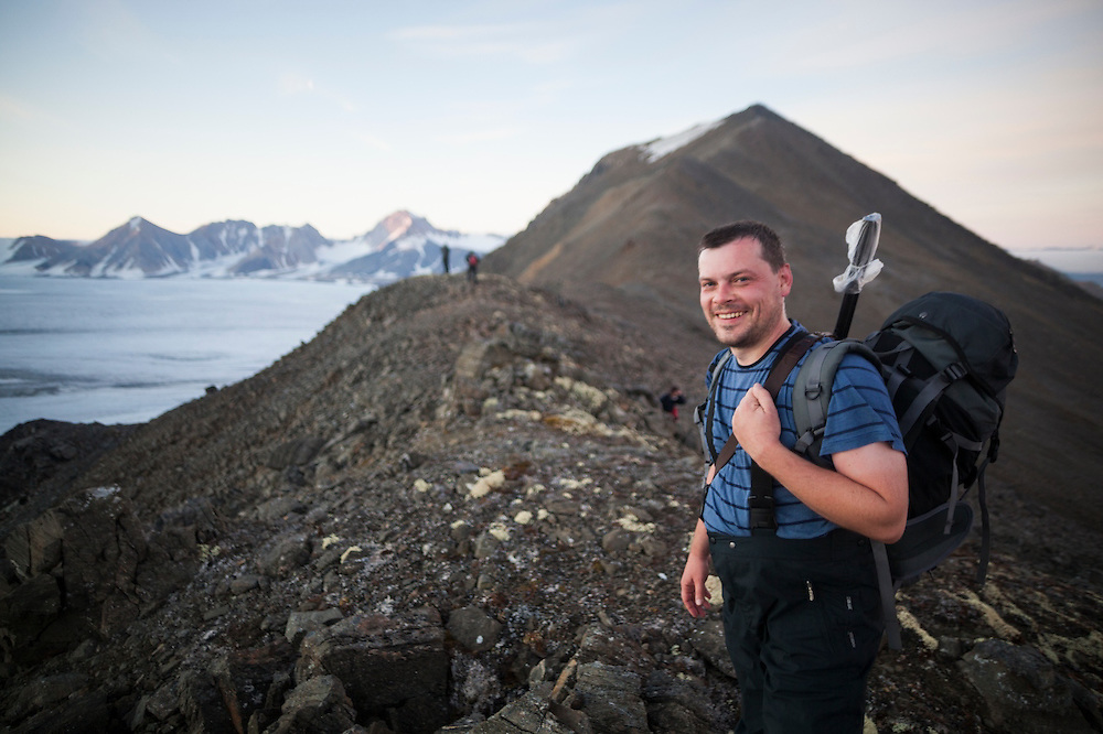 Geophysicist Grzegorz Karasinski stands with a gun at Arieskaret Pass during a sunset hike above the Polish Polar Station in Hornsund, Svalbard.