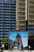 Passers-by and a construction hoarding showing the Foster-designed Principal Tower thats under construction on Shoreditch High Street, on 10th May 2017, in London, England.