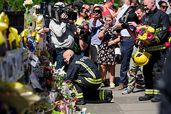 19/06/2017. London, UK. Firefighters who attended the scene of the fire join relatives of the victims and members of the public to observe minutes silence held near the scene of the Grenfell tower block fire. The blaze engulfed the 27-storey building killing dozens - with 34 people still in hospital, many of whom are in critical condition. Photo credit: Ben Cawthra *** Please Use Credit from Credit Field ***