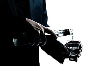 one caucasian man hands close up pouring white alcohol in a glass silhouette in studio isolated white background