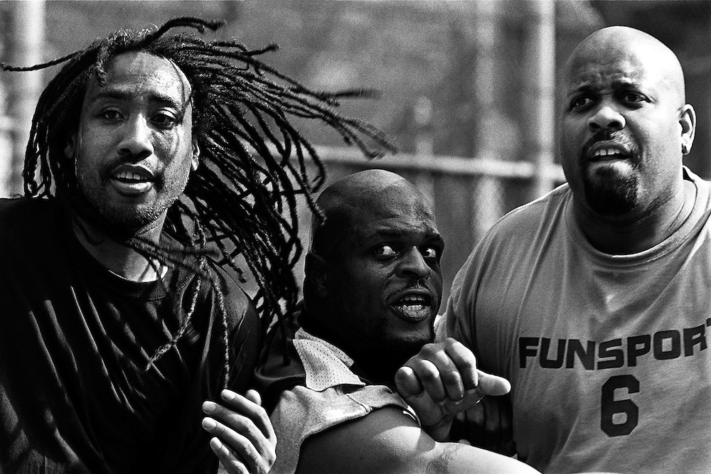 "March 30th 2005. New York, New York. United States..Located in the heart of Greenwich Village, the West 4th Street basketball Court, known as ""The Cage"", offers no seating but attracts the best players and a lot of spectators as soon as spring is around the corner..Half the size of a regular basketball court, it creates a fast, high level of play. The more people watch, the more intense the games get. « The Cage » is a free show. Amazing actions, insults and fights sometimes, create tensions among and inside the teams. The strongest impose their rules. Charisma is present..""The Cage"" is a microcosm. It's a meeting point for the African American street culture of New York. Often originally from Jamaica or other islands of the Caribbean, they hang out, talk, joke, laugh, comment the game, smoke… Whether they play or not, they're here, inside ""The Cage"". Everybody knows everybody, they all greet each other, they shake hands and hug: ""Yo, whasup man?"""