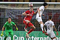 """Gareth Bale, second top, of Wales national football team heads the ball to make a pass against Edinson Cavani of Uruguay national football team in their final match during the 2018 Gree China Cup International Football Championship in Nanning city, south China's Guangxi Zhuang Autonomous Region, 26 March 2018.<br /> <br /> Edinson Cavani's goal in the second half helped Uruguay beat Wales to claim the title of the second edition of China Cup International Football Championship here on Monday (26 March 2018). """"It was a tough match. I'm very satisfied with the result and I think that we can even get better if we didn't suffer from jet lag or injuries. I think the result was very satisfactory,"""" said Uruguay coach Oscar Tabarez. Wales were buoyed by a 6-0 victory over China while Uruguay were fresh from a 2-0 win over the Czech Republic. Uruguay almost took a dream start just 3 minutes into the game as Luis Suarez's shot on Nahitan Nandez cross smacked the upright. Uruguay were dealt a blow on 8 minutes when Jose Gimenez was injured in a challenge and was replaced by Sebastian Coates. Inter Milan's midfielder Matias Vecino of Uruguay also fired at the edge of box from a looped pass but only saw his attempt whistle past the post. Suarez squandered a golden opportunity on 32 minutes when Ashley Williams's wayward backpass sent him clear, but the Barca hitman rattled the woodwork again with goalkeeper Wayne Hennessey well beaten."""