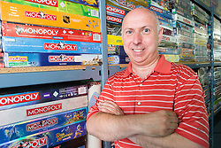 ** CAPTION CORRECTION Neil Scallan has spent an estimated £150,000 on monopoly boards, not £150,00 as stated in previous captions** <br /> © Licensed to London News Pictures. 24/07/2016. Crawley, UK.  Monopoly board game collector Neil Scallon with some of his 2200 unopened monopoly games, which he is hoping will set a Guinness World Record for the largest collection of Monopoly.  Scallan, who has been collecting for 10 years and estimates he has spent over £150,00 on the board games, is expected to set a  world record at the count later today (Sun) as the previous world record stands at around 500..  Photo credit: Grant Melton/LNP