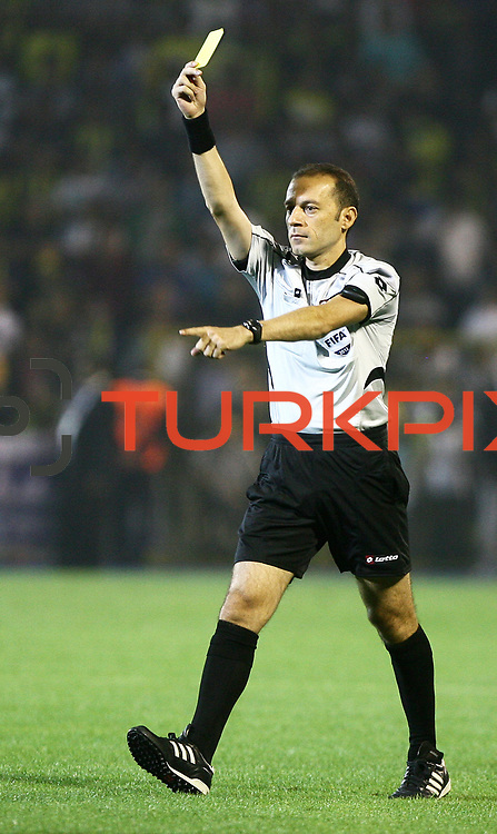 Refeere's Cuneyt Cakir shows a yellow card on Turkish Super Cup 2012 soccer derby match Galatasaray between Fenerbahce at the Kazim Karabekir stadium in Erzurum Turkey on Sunday, 12 August 2012. Photo by TURKPIX