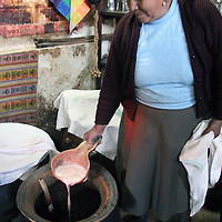 South America, Peru, Cusco. Peruvian woman  making traditional Chicha corn beer.