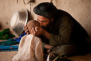 An Afghan man reassures his child during a serach of his family's compound by U.S. Marines and Afghan National Army soldiers.