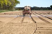 Farm machinery spraying an arable field of bare soil, Shottisham Suffolk, England, UK