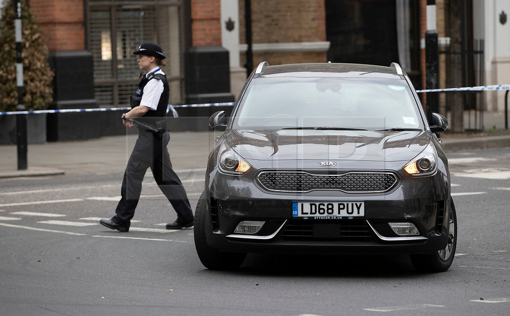 © Licensed to London News Pictures. 03/06/2020. London, UK. Police stand near an abandoned Kia Niro mini cab on Sloane Square. It is being reported that two people have been injured in the incident where it is thought a car mounted the pavement. Photo credit: Peter Macdiarmid/LNP