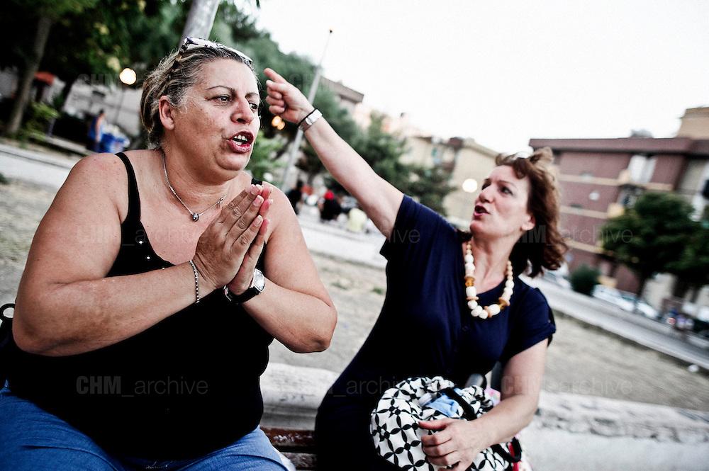 Due donne del  quartiere Tamburi parlano dell'Ilva, indicando i parchi minerari a ridosso della zona. Christian Mantuano/OneShot
