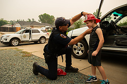 Fire Marshall Craig Wittner adjusts a plastic fire hat to returning resident Cayden Campbell, 6, during the Carr fire on Monday, July 30, 2018, in Redding, Calif. Photo by Paul Kitagaki Jr./Sacramento Bee/TNS/ABACAPRESS.COM