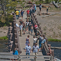 Tourists cross the Firehole River at Midway Geyser Basin in Wyoming's Yellowstone National Park.