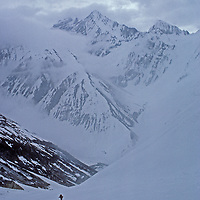 A ski mountaineer - dwarfed by India's Great Himalaya Range - climbs out of the Warwan River Gorge as a storm approaches and avalanche danger builds.