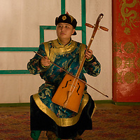 A musician in the famous Mongolian dance and musical troupe, Tumen Ekh, plays the horsehead fiddle in Ulaanbaatar.