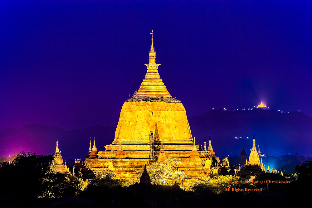 Golden Stupa, Purple Sky: Buddhist temples are as numerous and pervasive as the faith and this gigantic, illuminated golden Stupa makes the point as it dominates both the people and landscape; captured under the purple sky of dawn, Bagan Myanmar.