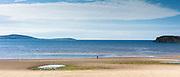 Lone figure, a fisherman, strolls along Little Gruinard remote sandy beach in the West Coast of Scotland