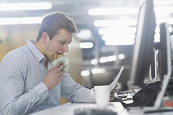 Young businessman eating toasted bread and reading document in office, Freiburg im Breisgau, Baden-Wuerttemberg, Germany