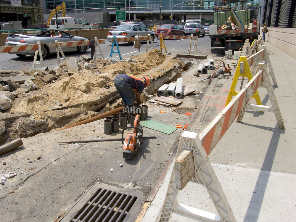 construction workers breaking up the street to put some new piping underground