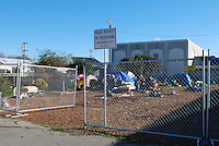 New fencing encloses the lot once occupied by Tents on the Gardens, a well-organized community of homeless people. On Thursday, January 31st, Salinas city workers, health officials and police conducted an early morning sweep of Chinatown,  removing encampments on the street and in lots between buildings all along Soledad Street.
