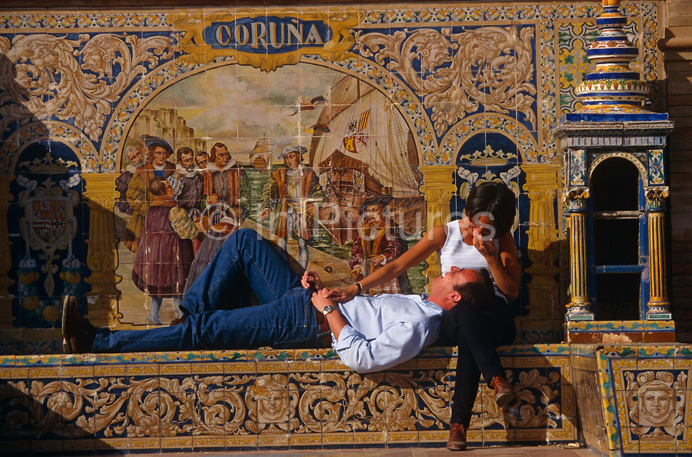 A young professional couple lie in the sun and share a humerous moment. They sit with their backs to intricate and delicate tiling which depict the Spanish province of Coruna, at the Plaza de España, Seville, Andalucia, Spain. The lady is sitting with her partner's head in her lap, indicating romance and contentedness as she suppresses a giggle. They are both lit by strong sunshine and gives the impression of a perfect moment in their loving relationship. This semicircular enclosure was built by Aníbal González, the great architect of Sevillian regionalism, for the Ibero-American exposition held in 1929.