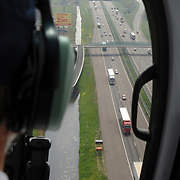 NLD/Rotterdam/20070423 - Rondvlucht boven Rotterdamse in een helicopter, snelweg, vrachtwagens, auto's