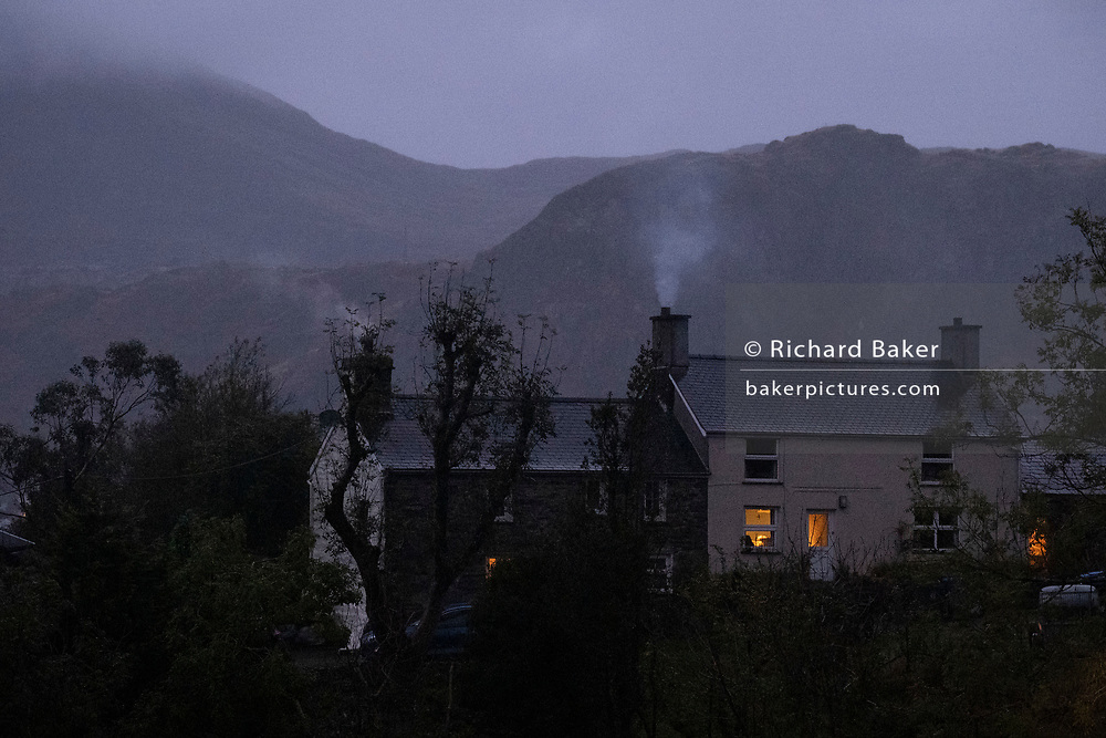 With a backdrop of mountains associated with the slate mining industry, smoke rises from the chimney of a property, on 2nd October 2021, in Blaenau Ffestiniog, Gwynedd, Wales. In 2021, the derelict slate mines around Blaenau Ffestiniog in north Wales were awarded UNESCO World Heritage status. Mined for roof tiles since Roman times, the industry's heyday was the 1890s when the Welsh slate industry employed approximately 17,000 workers, producing almost 500,000 tonnes of slate a year, around a third of all roofing slate used in the world in the late 19th century. Welsh slate was used on buildings across the globe including Westminster Hall in London's Houses of Parliament. In 1830, half the buildings in New York had roofs made of Welsh slate. However, only 10% of slate was ever of good enough quality and the surrounding mountains now have slate waste and the ruined remains of machinery, workshops and shelters have changed the landscape for square miles.