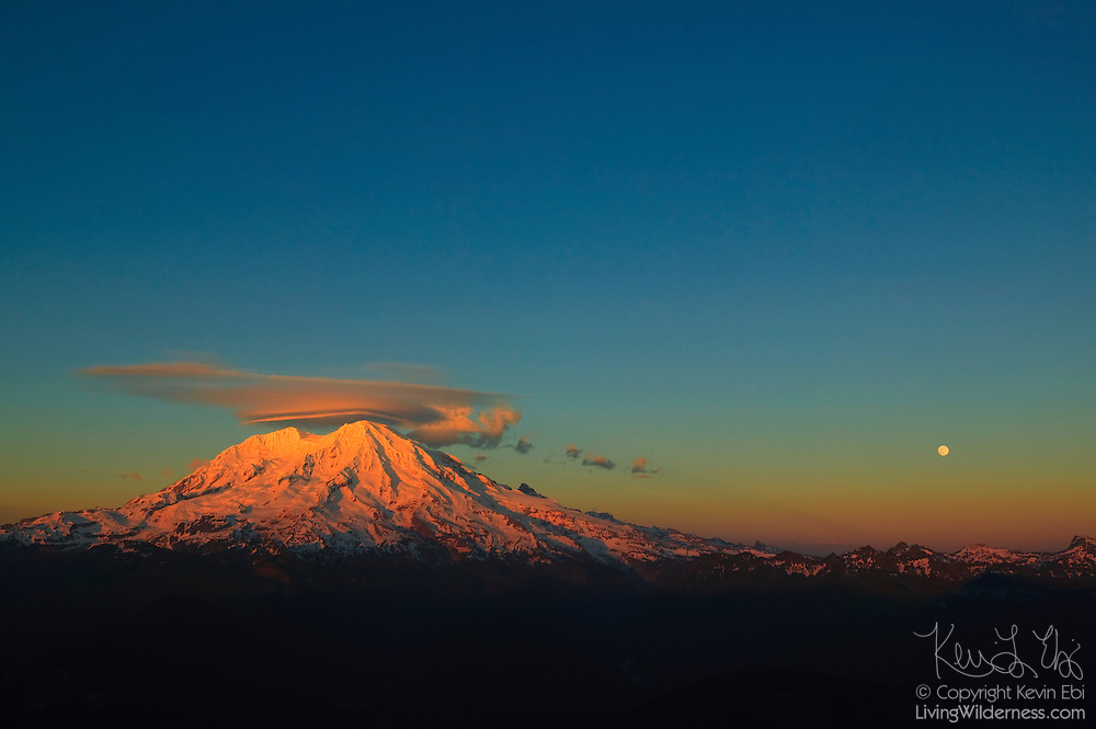 A lenticular cloud forms over the summit of Mount Rainier as the full moon rises over the Tatoosh Range in Washington state.