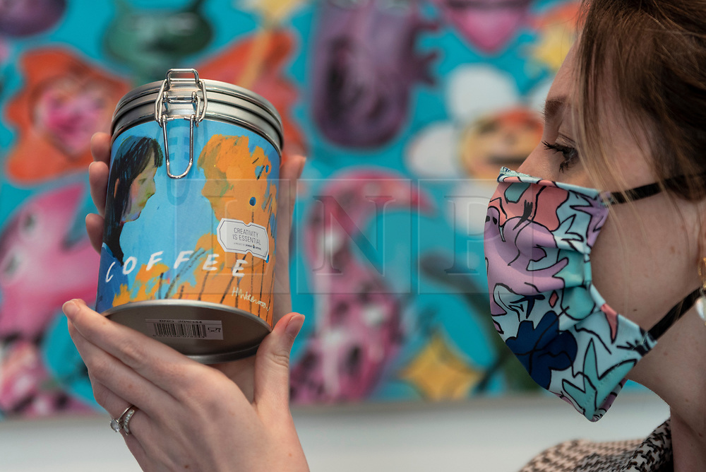 © Licensed to London News Pictures. 20/04/2021. LONDON, UK. A staff member poses at the reopening of the Design Museum's shop in Kensington High Street which is marked by a pop-up supermarket, wrapped in designer Camille Walala's unique visual style and colours.  For five days, items such as tins of kidney beans, tea, coffee, bread, pasta sauce, porridge oats, rice, toilet paper and washing up liquid are on sale and packaged in artworks created by a line-up of emerging artists.  All proceeds will go to the Design Museum's new Emerging Designer Access Fund, supported by BOMBAY SAPPHIRE.  Photo credit: Stephen Chung/LNP