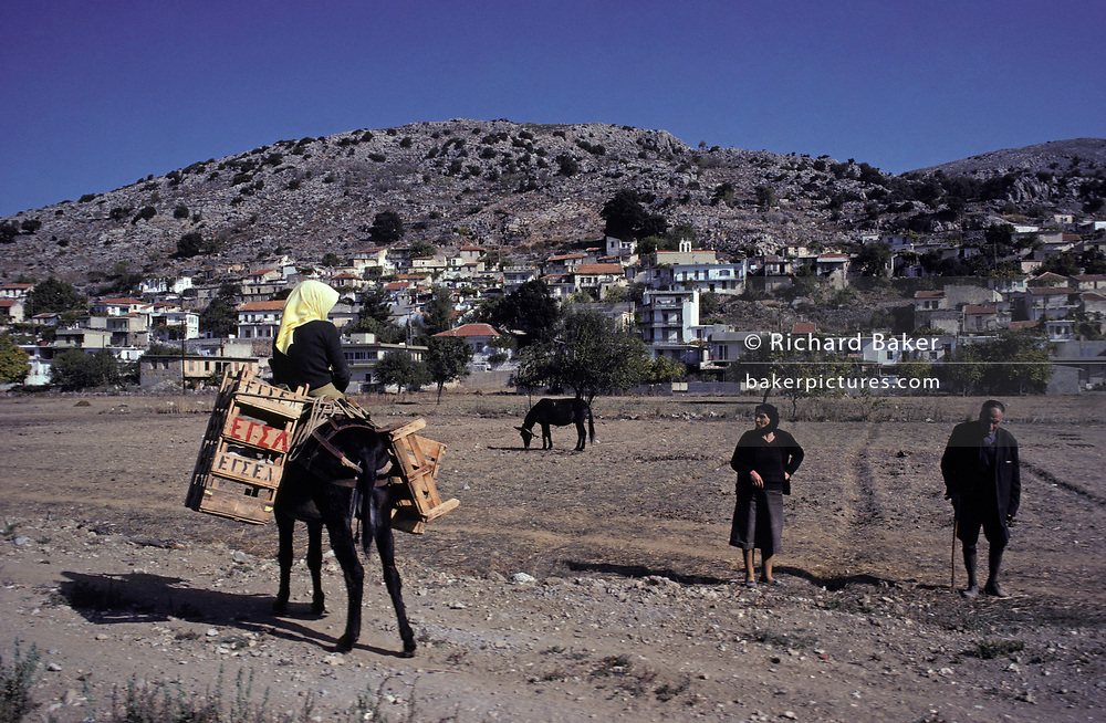 With the homes of their mountain community in the background, villagers in a field and riding a mule, converse in the middle of the day in rural Crete, on 13th April 1979, in Tzermaido, Lasithi Plateau, Crete, Greece.