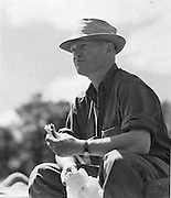 Gordon MacQuarrie eating lunch in the field, 1940.