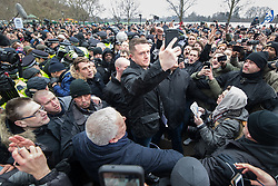 """© Licensed to London News Pictures . 18/03/2018 . London , UK . TOMMY ROBINSON (centre) takes a selfie with the crowd . 1000s including supports of alt-right groups such as Generation Identity and the Football Lads Alliance , at Speakers' Corner in Hyde Park where Tommy Robinson reads a speech by Generation Identity campaigner Martin Sellner . Along with Brittany Pettibone , Sellner was due to deliver the speech last week but the pair were arrested and detained by police when they arrived in the UK , forcing them to cancel an appearance at a UKIP """" Young Independence """" youth event , which in turn was reportedly cancelled amid security concerns . Photo credit: Joel Goodman/LNP"""