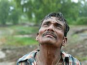 A local farmer looks up as the rain falls in the monsoon season, Goa, India