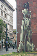A wall mural in Portland, Oregon, titled Capax Infiniti, depicts a woman from the back painted in green on the side of a red brick building with her hands behind her back.