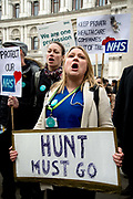Fourth 48 hour strike by junior doctors over proposed changes to their contracts with the NHS on Westminster April 6th 2016 in Westminster, London, United Kingdom. A woman protester holds a placard saying 'Hunt must go'.