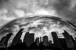 Black and white Chicago Cloud Gate The Bean sculpture with Chicago skyline reflection. The Cloud Gate sculpture was created by artist Anish Kapoor and is located in Millenium Park in downtown Chicago. Cloud Gate is also called The Bean, Chicago Jelly Bean, Silver Bean, Kidney Bean, and Giant Bean.