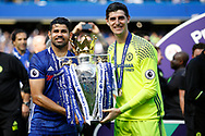 Chelsea Forward Diego Costa (19) and Chelsea Goalkeeper Thibaut Courtois (13) celebrate with the trophy during the Premier League match between Chelsea and Sunderland at Stamford Bridge, London, England on 21 May 2017. Photo by Andy Walter.