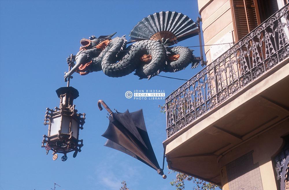 Dragon and umbrella statues projecting from wall in Las Ramblas; Barcelona,