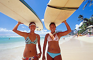 Two surfer girls emerging from the water after a session carrying their long boards on top of their heads at Waikiki beach, Honolulu, HI