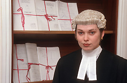 Portrait of female barrister wearing wig standing in front of legal briefs,
