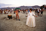 At the cocktail hour, a naked woman rubs fire on her body as another woman dressed in long white outfit walks around with an empty glass and a camera at Burning Man. Burning Man is a performance art festival known for art, drugs and sex. It takes place annually in the Black Rock Desert near Gerlach, Nevada, USA..