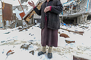 """Arina, an 88 years old Armenian lady whose husband died due to a heart attack following the scenery he'd seen after Azerbaijan air forces struck Nagorno Karabakh during 44 days of the war in 2020. Being the 2nd wife of her late husband she doesn't have any children. She doesn't get to see her step-children either she said on Thursday, Jan 28, 2021. During our conversation, she repeatedly said: """"....take me to America."""" She lives in a halfway house that needs renovating. The bomb that struck her house devastated its structure, she now lives in its rubbles. (Photo/ Vudi Xhymshiti)"""
