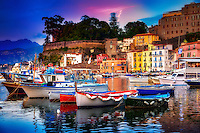 """""""Magic hour lights Marina Grande Sorrento""""…<br /> <br /> Arriving in Sorrento in late spring, the sunlight colorfully lingered before surrendering to the famous Sorrento moon.  One of the highlights of my Italian journey was stumbling upon the tiny Marina Grande fishing village. It was as if I'd walked back in time and merged into this ageless world with its own pace and traditions. Life here seemingly has its own rhythm- a strongly united community tenaciously anchored to its family principles, hard work, and religious traditions. They love the sea and live in symbiosis with it; here time seems to move more slowly than anywhere in the world.  In 1558 the Turks plundered the town of Sorrento, and after the Saracens left the inhabitants constructed a solid town wall. My eyes were blessed with an extraordinarily beautiful canvas as a permanent smile measured my face, and my camera gazed upon this tiny bay nestled within the bygone fishing village.  I meandered about cautiously, glancing at fisherman humbly repairing their nets.  At the heart of the Marina is the Church of Sant'Anna, patron saint of the village. Restaurant Zi' Ntonio a Mare, which jutted out into the bay, was crowded with hungry guests and serenaded by an Italiano singer who, ironically, was singing Dean Martin songs which echoed throughout the bay;  guests and this photographer were delightfully enchanted.  I gently creeped along the water's edge, and tried to capture the perfect, yet very personal portrait of this piccola baia italiana della perfezione (Italian small bay of perfection).  As night fell, the water reflections and resting fishing boats posed for a few more images as fish jumped for their dinner!  It was time to enjoy the gifts of the day's catch at Ristorante di """"Zi'Ntonio Mare.  The epicureo delights, especially the calamari, olive bread, wine, and the main course of Il pesce San Pietro (The St. Peter's fish), was authentic perfection…just like this perfect piccola bay of Marina Grande"""